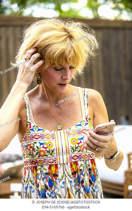 A pretty 42 year old blond woman looking at her cell phone
