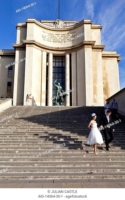Newlyweds dance down the steps of the west wing of the Palais de Chaillot, Paris, France. The Palace was designed in Neo-Classical style for the 1937 World's...