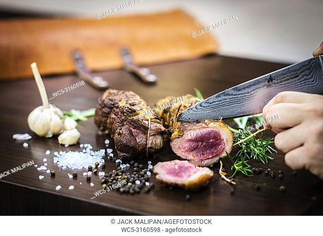 serving carving roast pork meat roll meal in rustic style with seasonings
