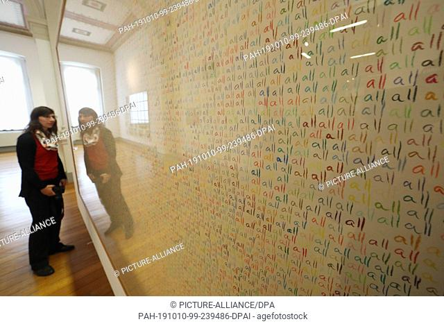 """10 October 2019, Thuringia, Altenburg: A visitor looks at a wall on which the word """"""""all"""""""" is written in different colours at the press conference for the..."""