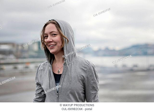 Portrait of young female runner wearing hoody on windy dockside