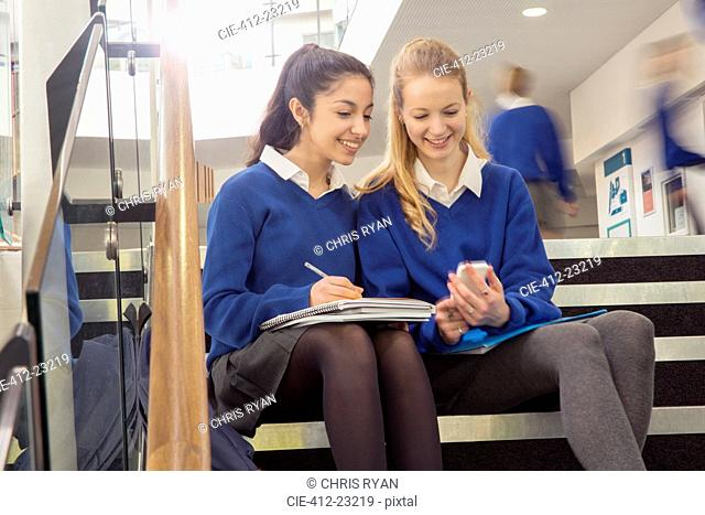 Two female students wearing blue school uniforms sitting on steps in school corridor and looking at mobile phone