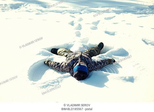 Caucasian boy making snow angel