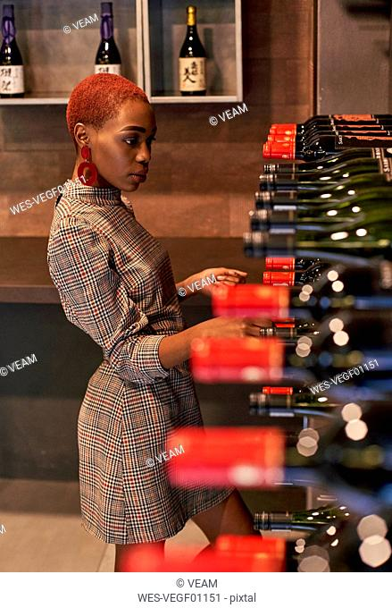 Young woman looking for a bottle of wine on her cellar