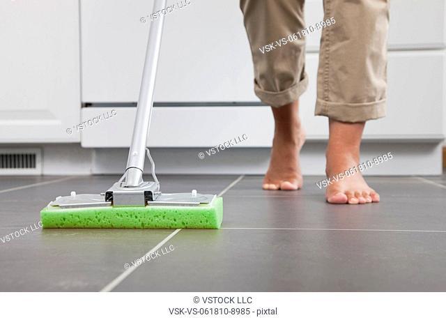 USA, Illinois, Metamora, Barefoot woman cleaning kitchen floor, low section