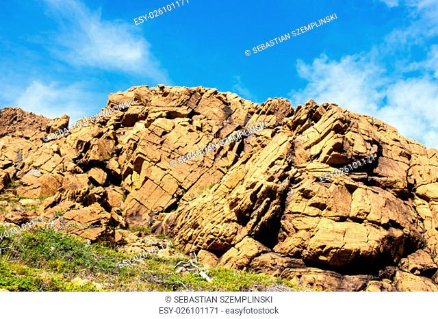 Large irregular cracked rock formation against partly cloudy blue sky, with green shrubs at base, at Tablelands, Gros Morne National Park, Newfoundland, Canada