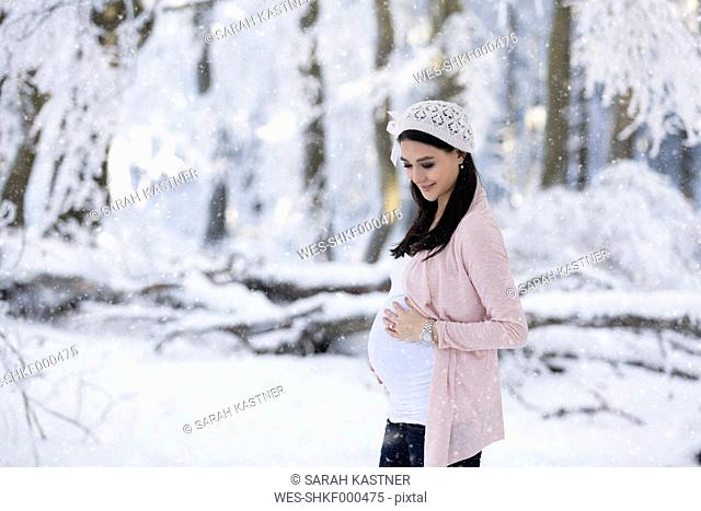 Smiling pregnant woman outdoors in snowfall