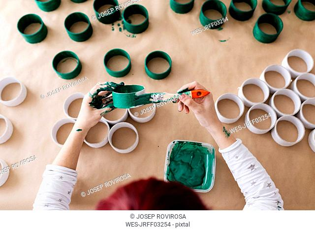 Top view of woman's hands painting a roll of cardboard with a green brush
