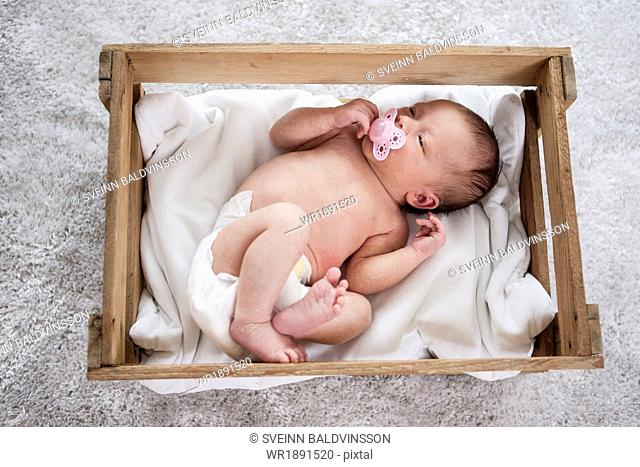 Newborn baby laying asleep with pacifier in mouth
