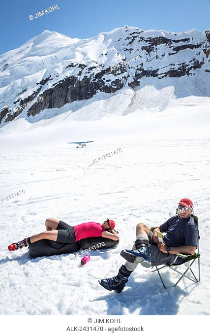 A couple relaxes while awaiting a ski plane pick up on the Ruth Glacier in the Alaska Range, Summer