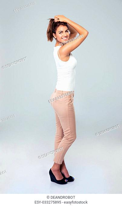 Full length portrait of a smiling businesswoman posing over gray background. Looking at camera
