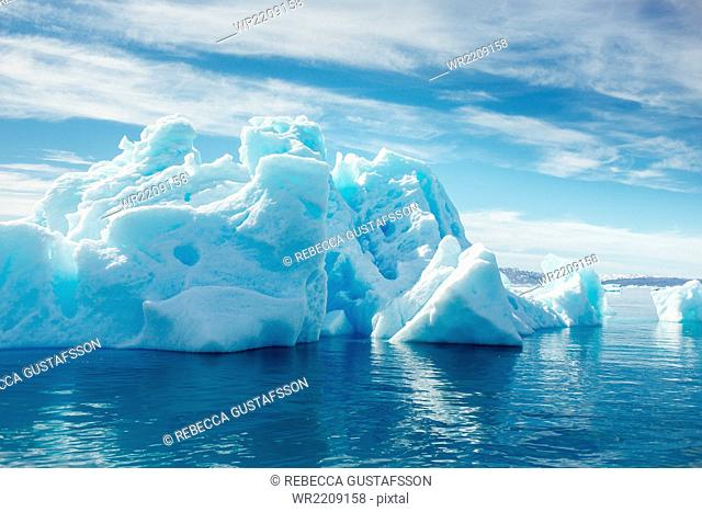 Majestic icebergs floating on sea against cloudy sky
