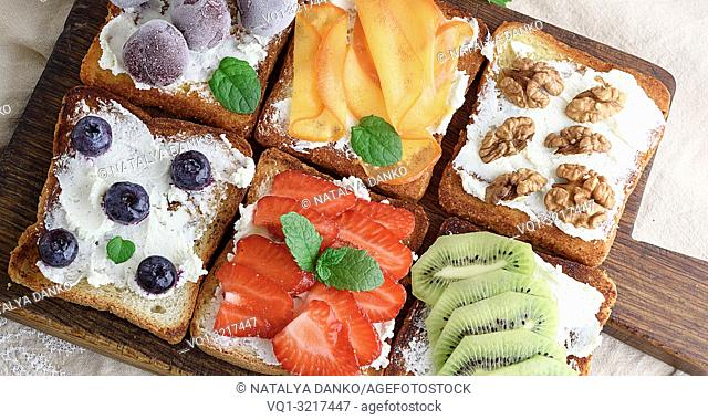French toasts with soft cheese, strawberries, kiwi, walnuts, cherries and blueberries on a brown wooden board