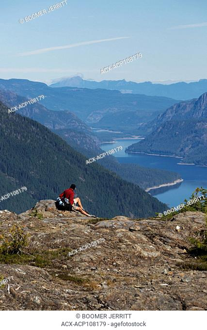 A lone male hiker relaxes at a viewpoint on the Flower Ridge trail overlooking Buttle Lake in Strathcona Park. Vancouver Island, British Columbia, Canada
