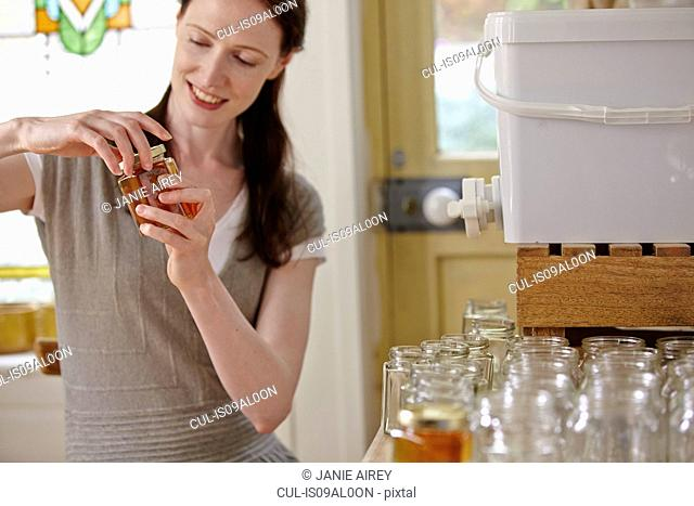 Female beekeeper in kitchen, bottling filtered honey from beehive