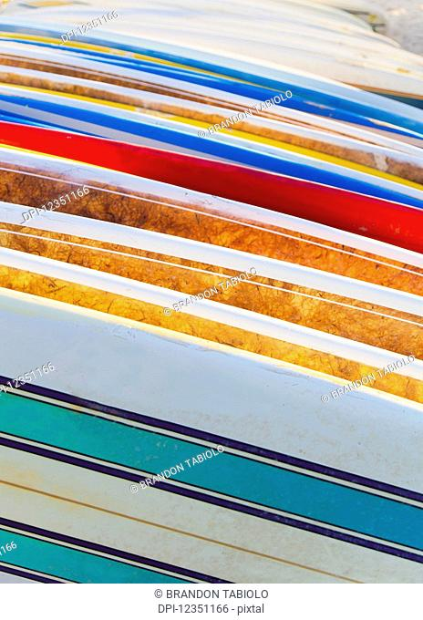 A stack of colourful longboard surfboards placed on the beach,; Waikiki, Oahu, Hawaii, United States of America