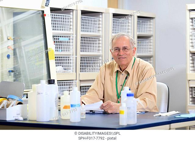 Engineering professor correcting papers in chemical laboratory