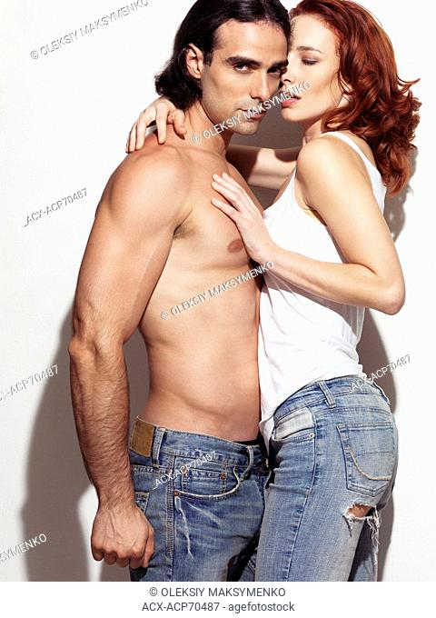 Expressive portrait of a sexy young man with bare torso wearing jeans embracing a young red haired woman in tank top. Isolated on white background