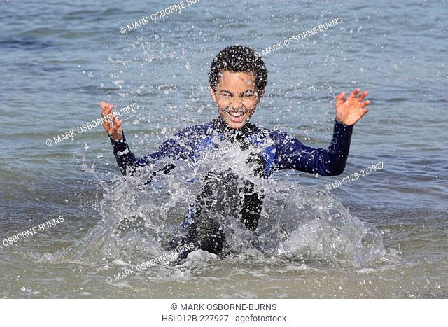 Young boy 11 years outdoors splashing in the sea