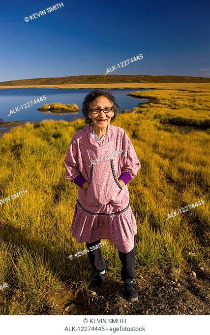 Native Alaskan elder woman wearing an Atigik standing on the Tundra with a small lake in the background, Fall, Kotzbue, Arctic Alaska, USA