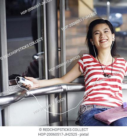 Portrait of a young woman listening to an MP3 player and smiling