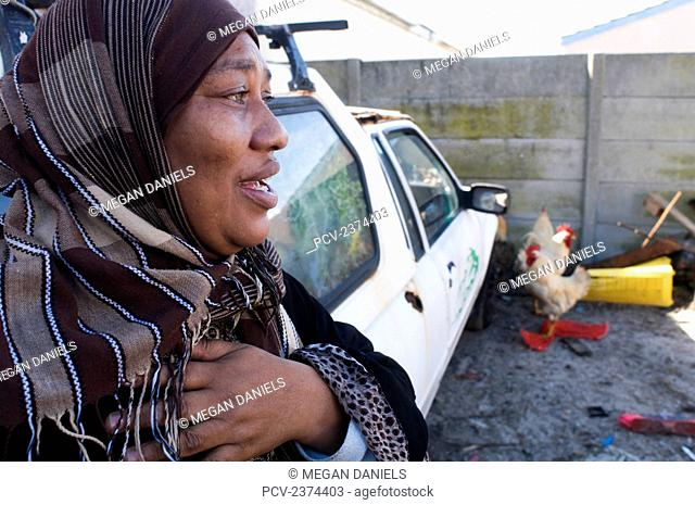 A woman wearing a headscarf standing beside a parked vehicle with chickens in the yard; Mfuleni, South Africa