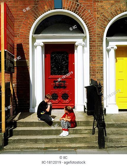 Children sitting in front of Georgian doors, Fitzwilliam Square, Dublin, Co Dublin, Ireland