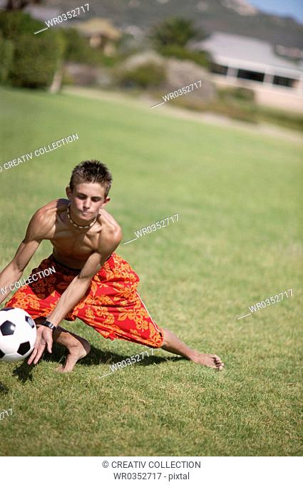 teenagers playing soccer on a field