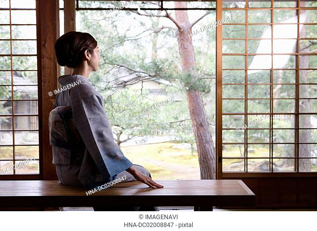 Young Japanese woman in kimono sitting on bench while looking at Japanese garden