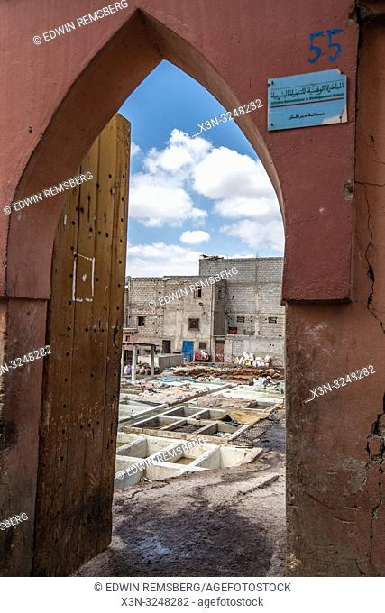 View through arch of doorway leading to pits full of solutions used to convert animal hides into tanned leather at tannery, Marrekech, Morocco