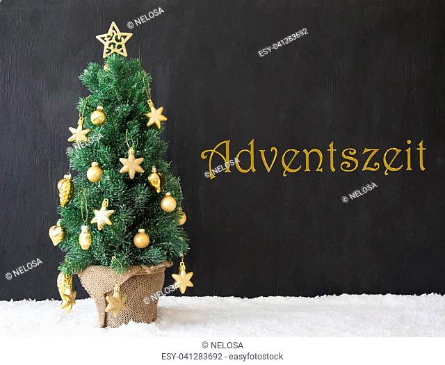 German Text Adventszeit Means Advent Season. Golden Decorated Christmas Tree With Black Concrete Or Cement Background. Modern Urban Style With Snow