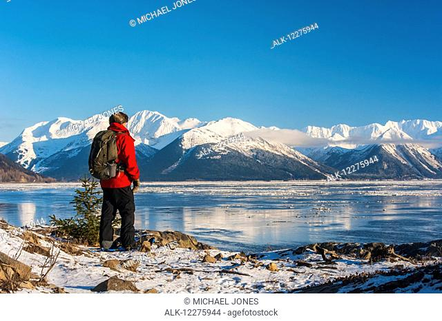 A man snowshoeing along the Cook Inlet with Kenai Mountains in the background, Southcentral Alaska, Winter
