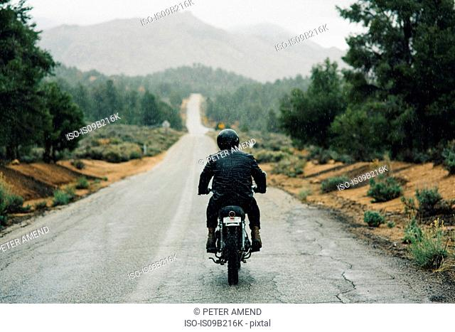 Rear view of motorcyclist riding motorbike on open road, Kennedy Meadows, California, USA