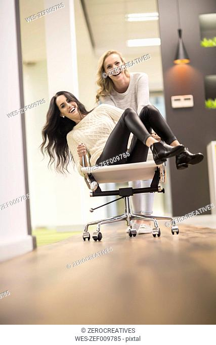 Young woman pushing her friend sitting on svivel chair through the office