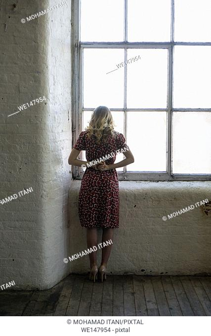 Rear view of a woman wearing vintage red dress standing by the window looking out