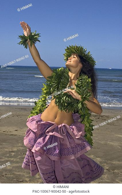 Hula dancer with haku lei in traditional outfit on beach, ocean background