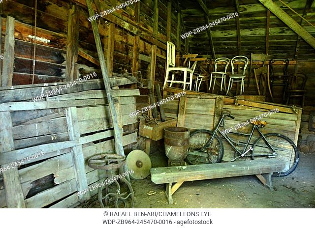 An old barn interior with vintage farm tools and retro old bike. Photo by Rafael Ben-Ari/Chameleons Eye