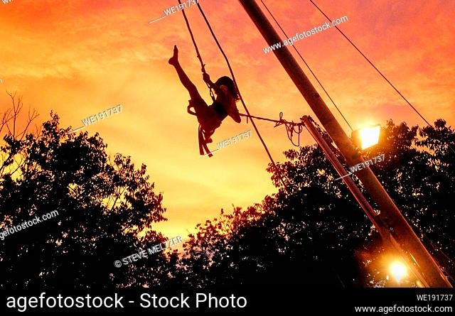 A young girl pumps her legs high in the air to push her rope swing high into the air of an evening sunset, South of France near Pezenas
