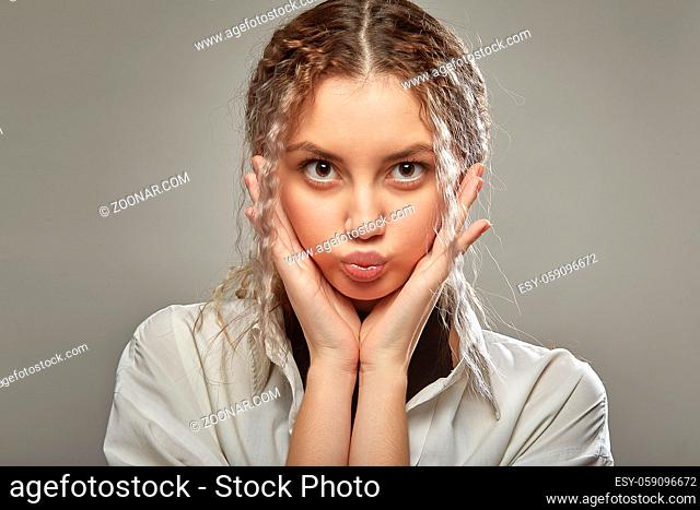 fun pretty girl on gray background making duck face