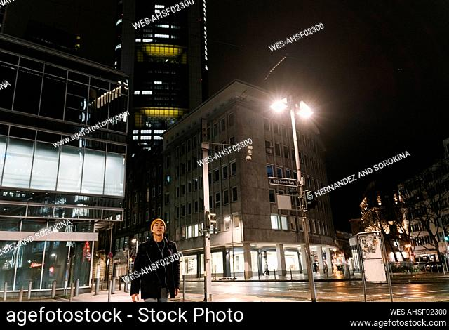 Man with yellow hat and earphones walking in the city at night
