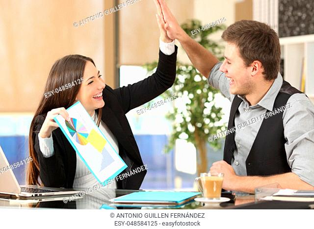 Successful coworker showing a growth graph celebrating good results and giving high five in an office interior