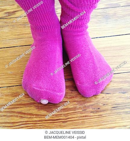 Girl's toe peeking out from hole in sock