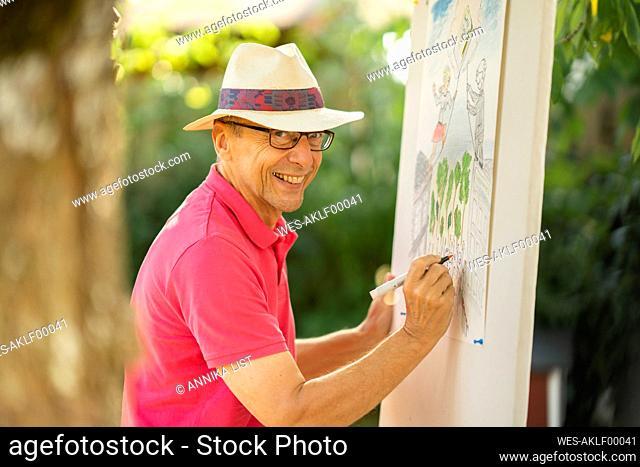 Happy senior wearing hat drawing in garden