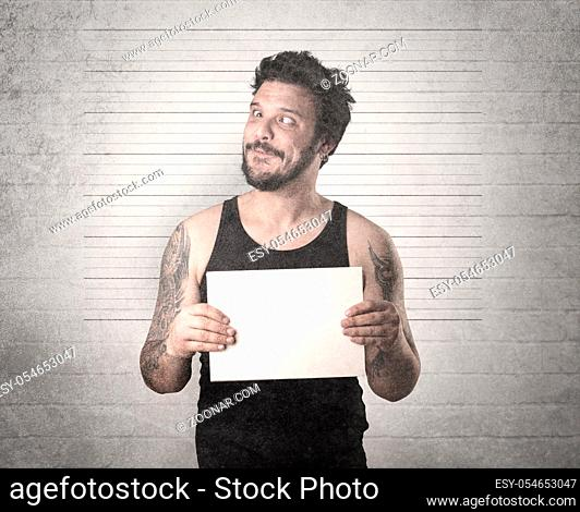 Gangster in front of a wall with table on his hand