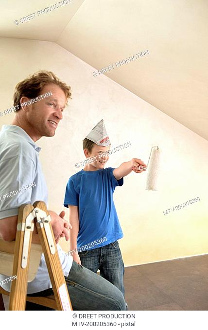 Father young boy painting decorating room happy
