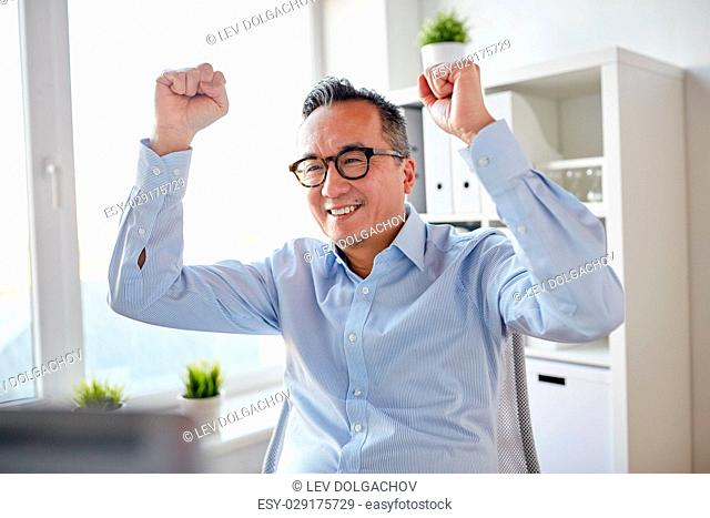 business, people and success concept - happy businessman celebrating victory at office