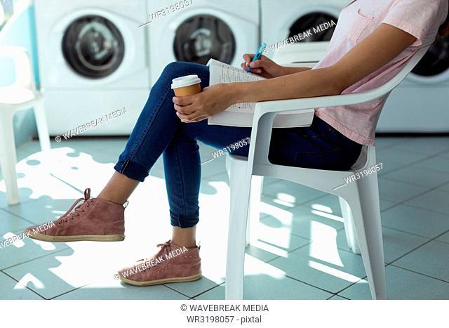 Woman with coffee cup writing in the book at laundromat