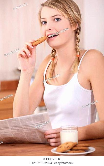 Woman with milk, cookies and newspaper