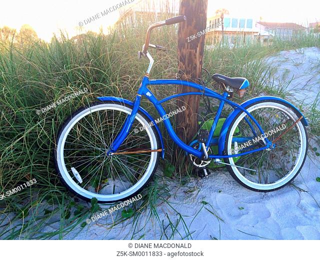 A bicycle chained to a post at the beach, Jacksonville Beach, Florida, USA