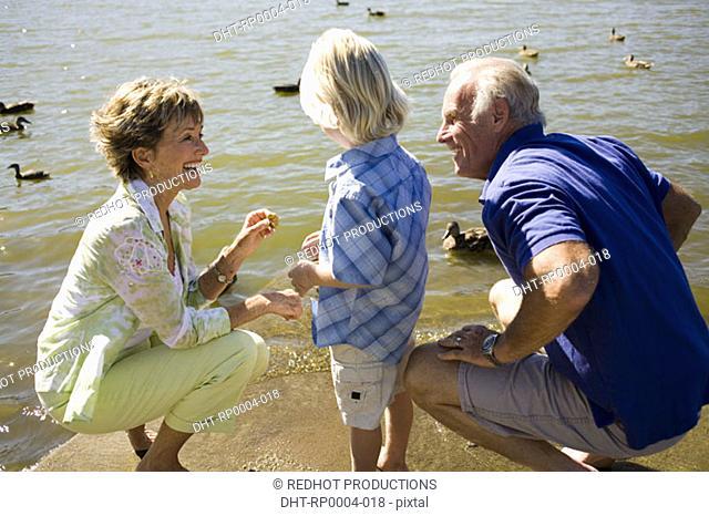 Grandparents and grandchild by lake